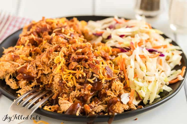 black plate of crockpot bbq chicken and coleslaw with fork sticking into chicken close up