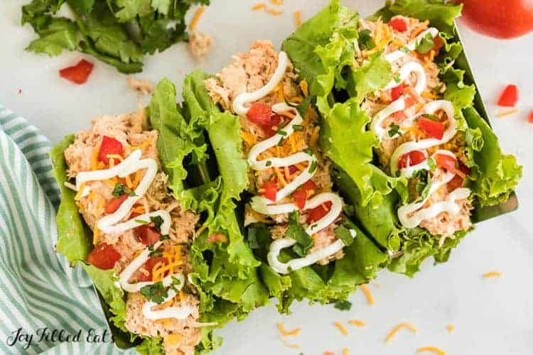 three lettuce wrapped crockpot chicken tacos drizzled in sour cream from above