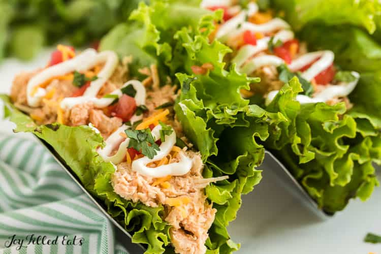upright lettuce wrapped crockpot chicken taco drizzled in sour cream close up