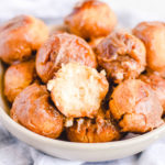 a bowl of keto donut holes with one missing a bite