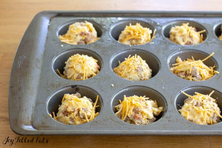 cheese topped muffin batter in a muffin tin