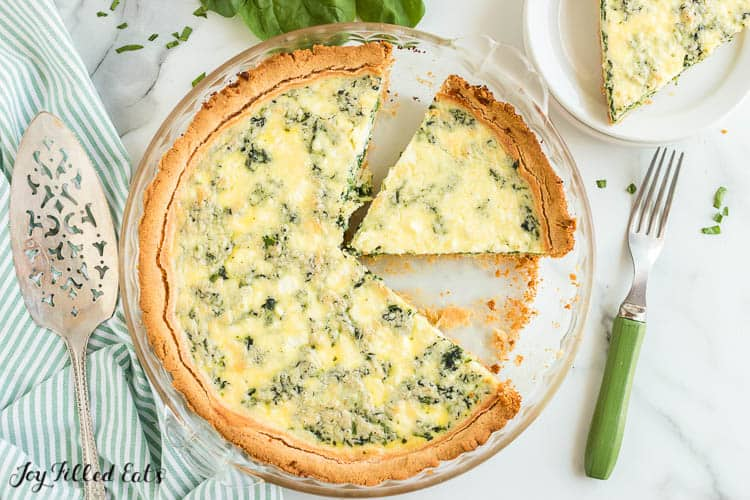 overhead view of pie plate filled with spinach and feta quiche with slice of quiche cut and offset from whole quiche