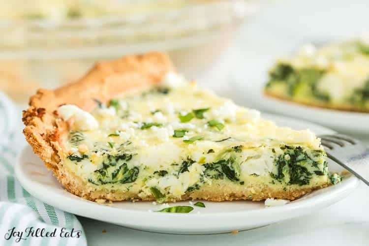 close up on slice of spinach and feta quiche on a plate with a fork
