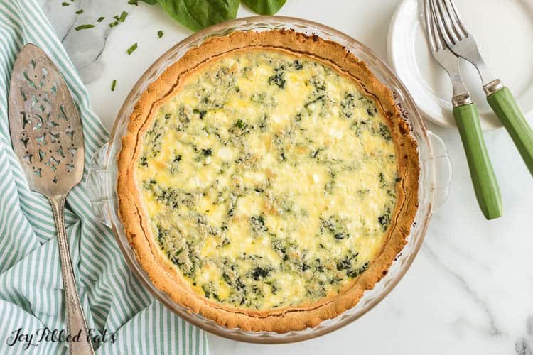 overhead view of pie plate containing spinach and feta quiche. pie plate is set next stack of plate with forks and a pie server on a decorative napkin