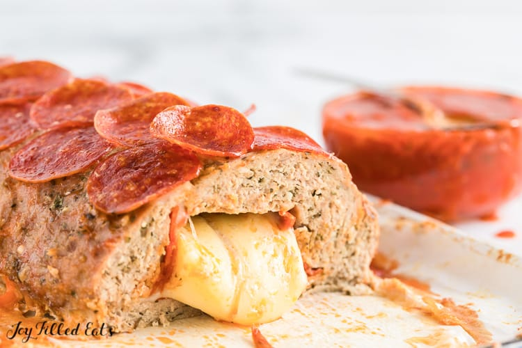 pepperoni topped meatloaf cut open to expose melted cheese oozing out of loaf