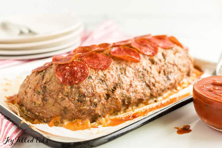 uncut meatloaf in a shallow baking dish next to a bowl of marinara sauce. top of meatloaf is covered in pepperoni slices