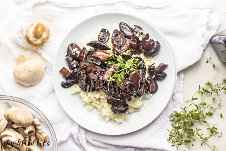 White plate of balsamic mushrooms served over riced cauliflower and topped with micro greens on a white table setting with a bowl of whole, raw mushrooms and a scattering of micro greens