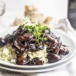 Plate of balsamic mushrooms served over riced cauliflower topped with micro greens