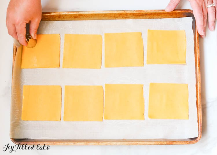 hand holding sheet pan with square slices of cheese lined in two rows, while other hand uses circle cutter to make shapes for cheese crackers