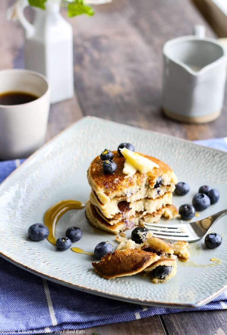 stack of blueberry ricotta pancakes center on a square plate cut in half by a fork with smaller pieces of pancake still on plate. Pancakes are topped with a pad of butter, drizzled in syrup and blueberries scattered on top and around plate