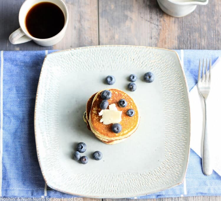 blueberry ricotta pancakes stacked center on a square plate topped with a pad of butter and blueberries scattered on top and around plate. Plate is set on a blue table mat next to a up of coffee