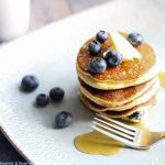 blueberry ricotta pancakes stacked center on a square plate topped with a pad of butter and blueberries scattered on top and around plate. syrup is drizzled on pancakes and plate with fork resting next to pancakes