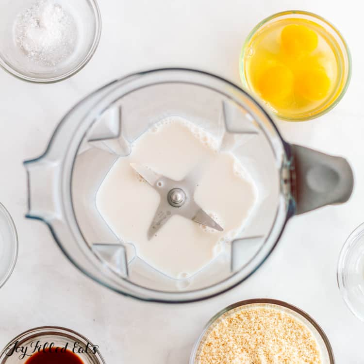 overhead view of blender pitcher with keto crepe ingredients added, surrounded by small bowls of other ingredients to be added into blender