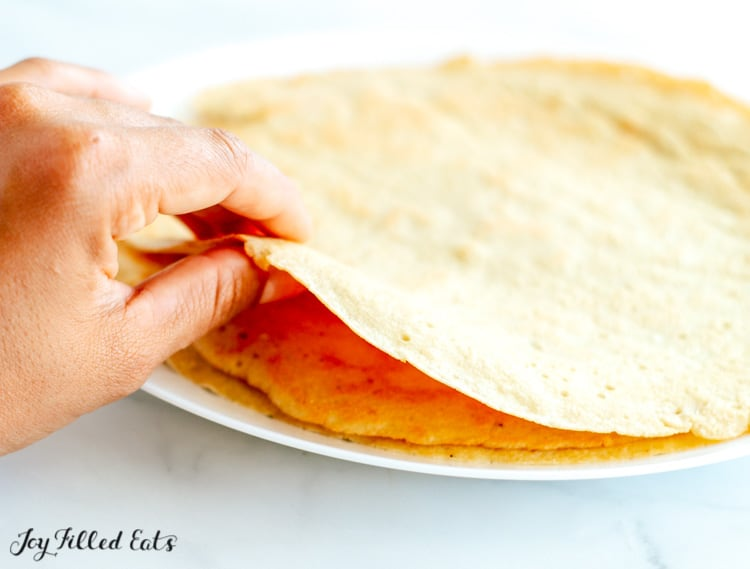 Hand picking up single crepe from pile of crepes on white dish to show the thinness of an individual crepe