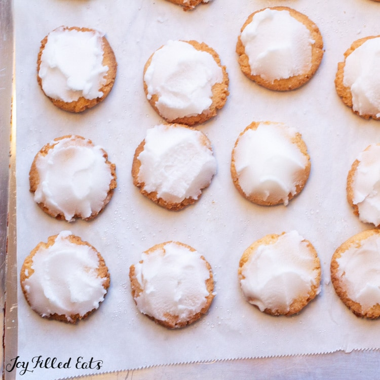 Overhead view of low carb iced lemon cookies lined on parchment paper