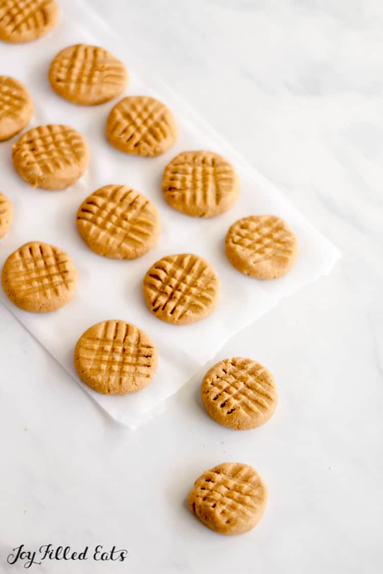 keto no bake peanut butter cookies lined in rows on parchment paper with two cookies on marbled table surface