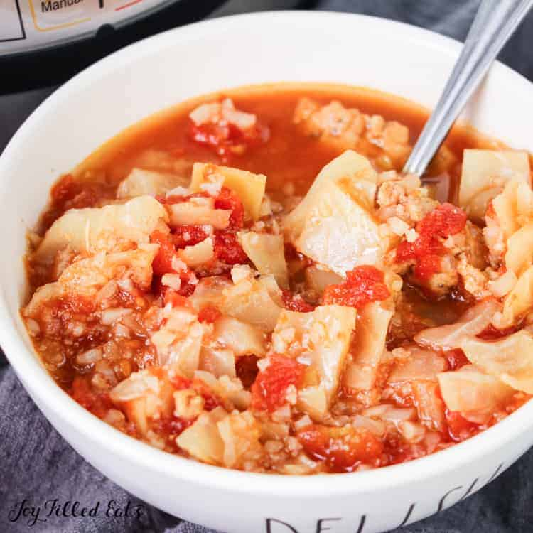 close up of cabbage roll soup in white soup bowl with spoon