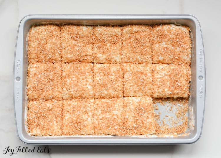 Sugar Free Marshmallows in baking pan coated in toasted coconut. Corner marshmallow is removed from baking dish