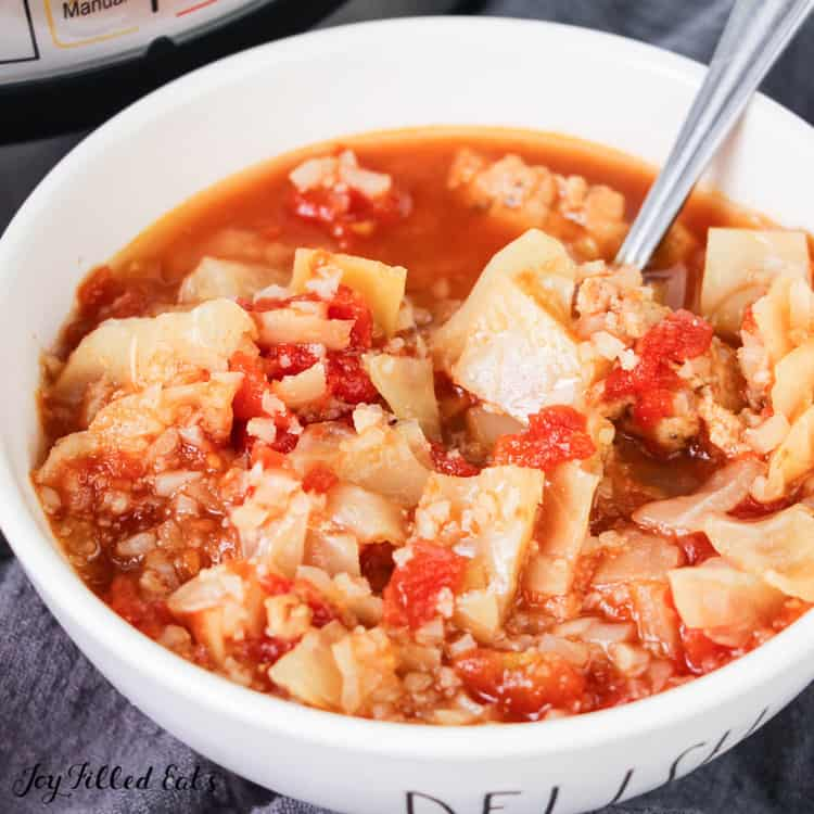 Cabbage roll soup in large white bowl with spoon