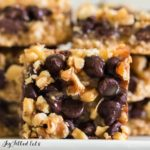 close up of magic cookie bar square in front of two stacks of magic cookie bars
