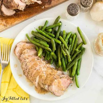 Slow cooked pork tenderloin slices covered in gravy fanned out on a white plate with a serving of green beans. Plate is next to a fork atop a yellow napkin, a cutting board with additional pork tenderloin slices, small pitcher of gravy and a salt and pepper shaker.