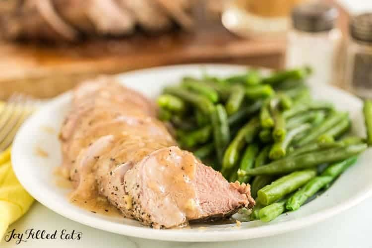 Plate of pork tenderloin slices covered in gravy fanned out next to a serving of green beans