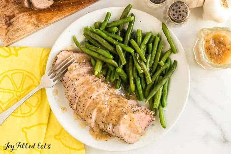Pork Tenderloins slices fanned out on plate with fork served with a side of green beans. Tenderloin slices are dripped in gravy. Plate is set next to a decorative yellow napkin.