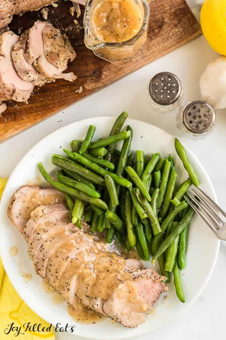 Slow cooked pork tenderloin slices covered in gravy fanned out on a white plate with fork and a serving of green beans. Plate is next to cutting board with additional pork tenderloin slices, small pitcher of gravy and a salt and pepper shaker.