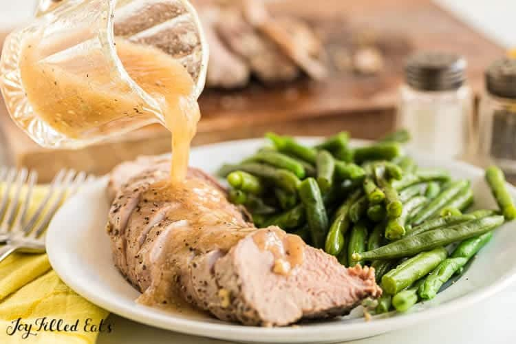 Small glass pitcher of gravy being poured onto pork tenderloin slices fanned out on a plate next to a side of green beans