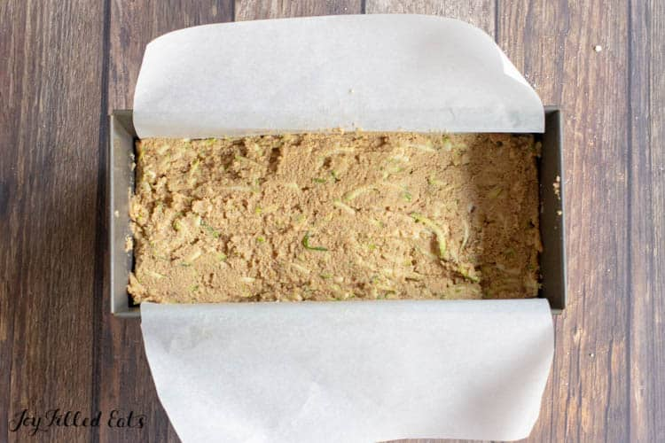 keto zucchini bread dough in a parchment lined bread pan before baking