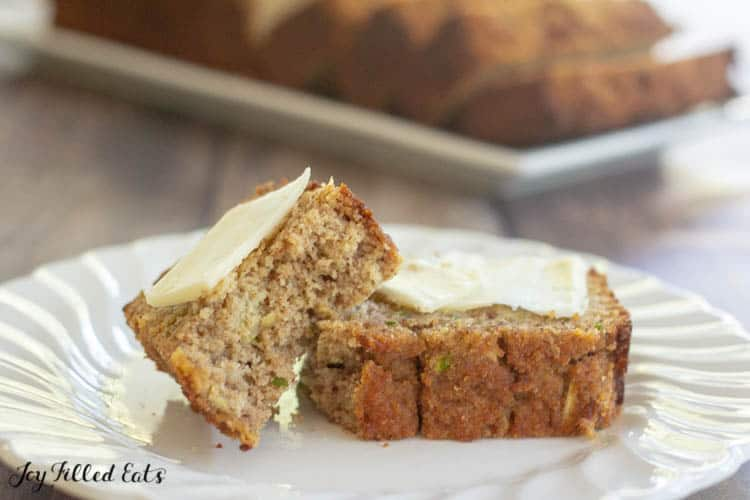 slice of low carb zucchini bread on a white plate torn in half. Each piece of bread is topped with a small spread of butter