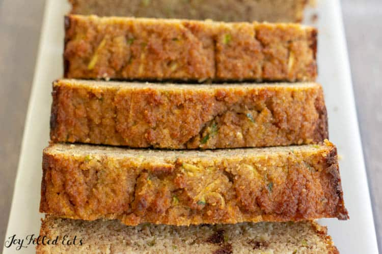 close up of keto zucchini bread sliced on a white, rectangular plate