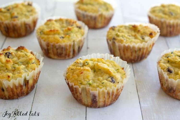 Chocolate Chip Zucchini Muffins in white paper liners on a white wood backdrop