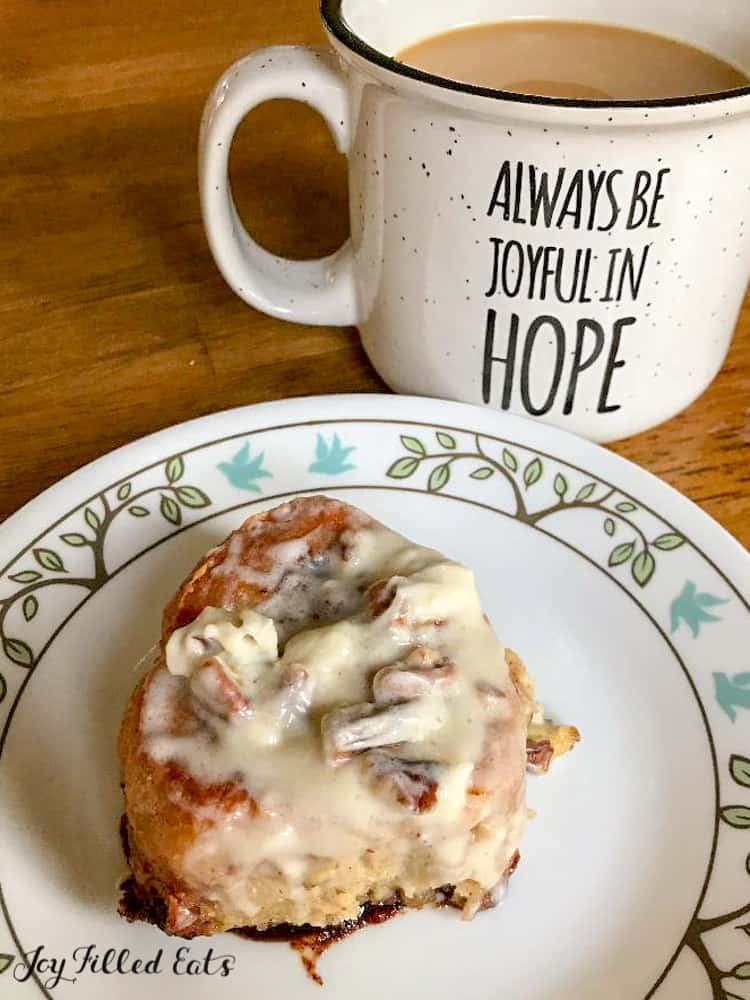 "one pumpkin spice cinnamon roll on white plate with decorative rim next to mug of coffee that reads ""always joyful in hope"""