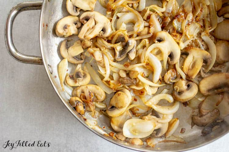 skillet filled with sauteed sliced mushrooms and sliced white onions