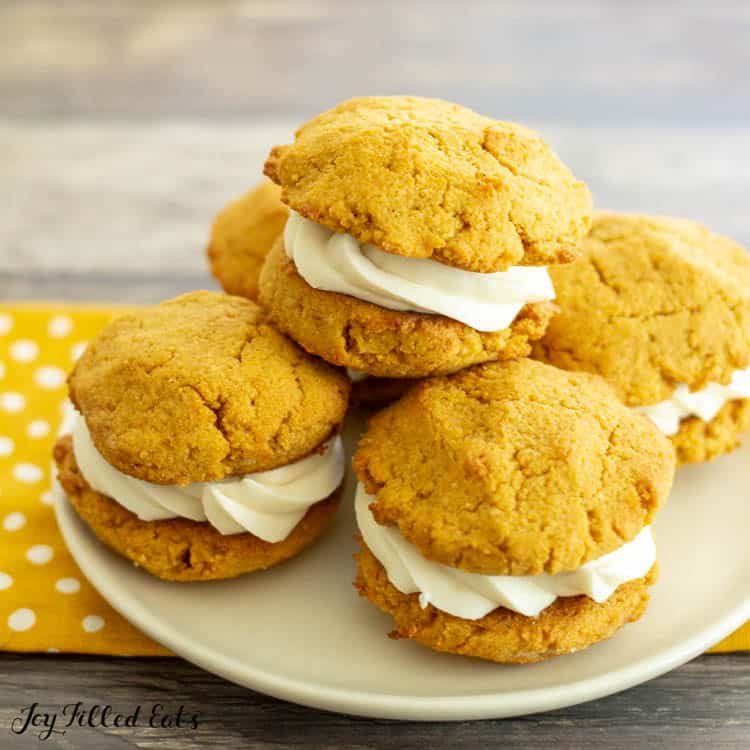 Pile of keto pumpkin cookies with filled cream cheese frosting on a plate placed on a yellow and white polka dot napkin