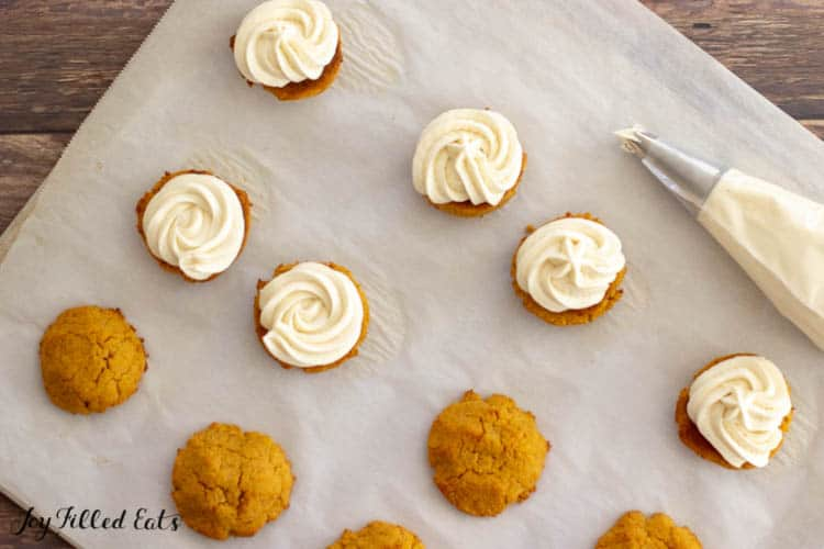 pumpkin sandwich cookies on parchment paper with cream cheese frosting piped on half the cookies along with full piping bag