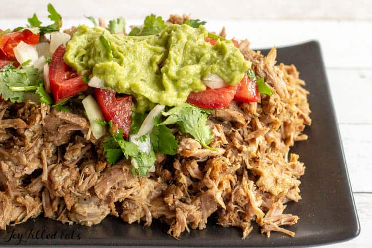 instant pot carnitas topped with a fresh tomato, onion and cilantro salsa along with a topping of guacamole