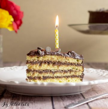 Slice of Keto Birthday cake layered with chocolate on a white plate. One lit yellow candle on the slice of cake.