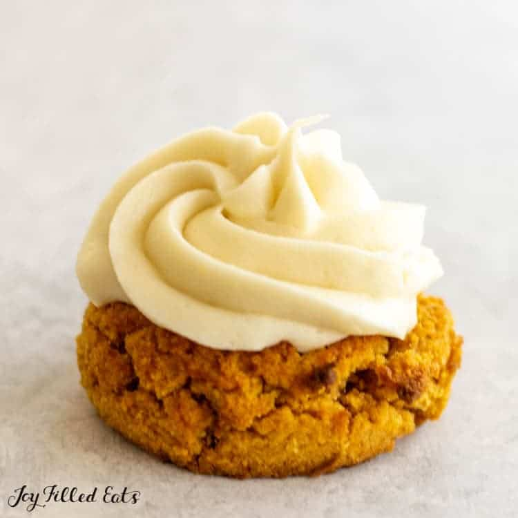 keto cream cheese frosting topping a small pumpkin cookie