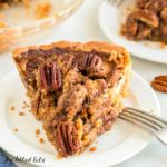Close up on keto pecan pie slice on white plate with fork