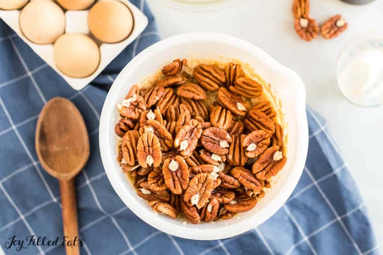 overhead view of mixing bowl filled with pecans atop pie filled. Bowl is placed on a blue plaid napkin with a wooden spoon and next to a carton of eggs, measuring cup and a few scattered whole pecans