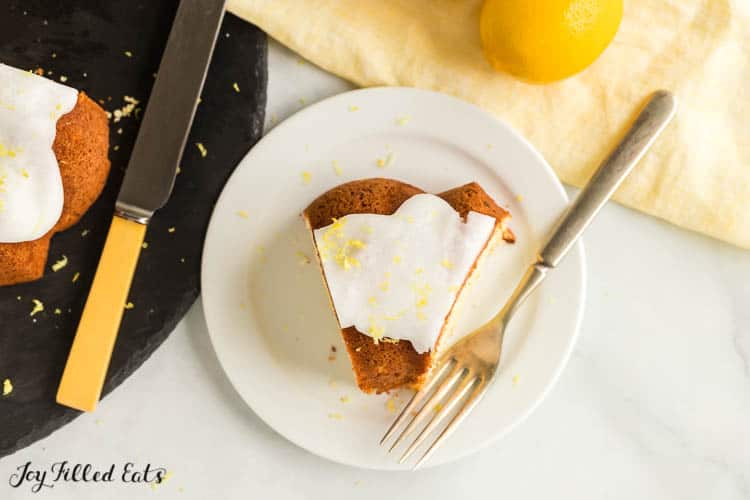 overhead view of white plate and fork with slice of lemon drizzle cake. Cake top is glazed with icing and sprinkled with lemon zest. Plate is situated on table next to napkin with a lemon and black cutting board with knife and more lemon drizzle cake.