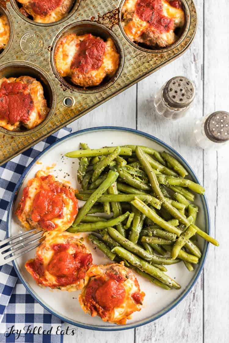 overhead view of muffin tin filled with mini meatloaves next to a salt and pepper shaker and a plate with three mini meatloaves, fork, and a large serving of roasted green beans