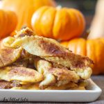 Close up of Keto Pumpkin Pie Twists on a white plate with pumpkins in the background