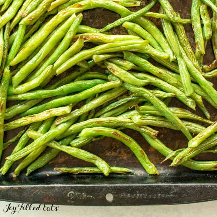 close up of roasted green beans on sheet pan