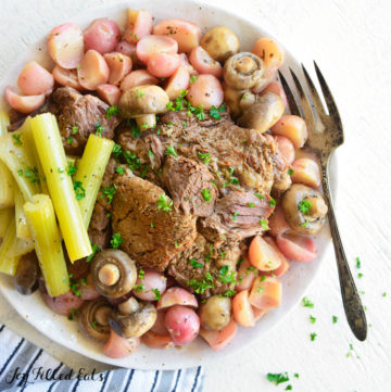 Large serving Plate of instant pot beef roast with celery, radishes and mushrooms. Large serving fork on plate.