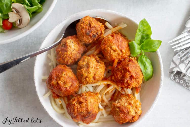 overhead view of meatballs atop spaghetti in white bowl with basil leaf