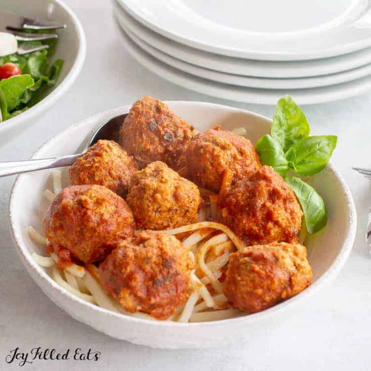 close up on white bowl full of spaghetti and meatballs garnished with basil