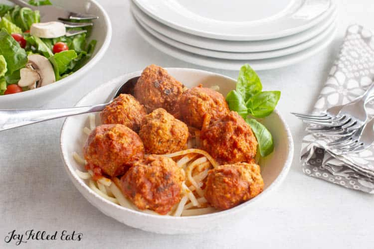 bowl of spaghetti and meatballs garnished with basil next to bowl of salad, stack of plates, and napkin with forks